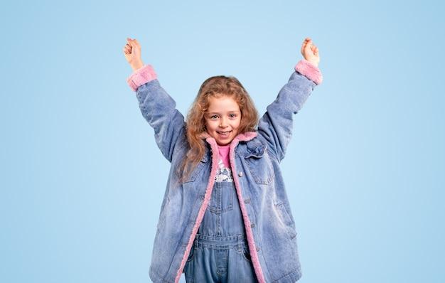 Wesoła Dziewczynka W Niebieskiej Ciepłej Dżinsowej Kurtce, Podnosząc Ręce I Patrząc Na Kamery, Stojąc Na Niebieskim Tle Premium Zdjęcia