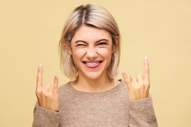 Wesoła, Energiczna, Stylowa Kobieta, Która Wystawia Język I Mruga, Wykonując Gest Diabelskich Rogów, Pokazując Uniwersalny Heavy Metalowy Znak Dla Ciebie Rock, Reprezentowany Przez Palec Wskazujący I Mały Uniesiony Darmowe Zdjęcia