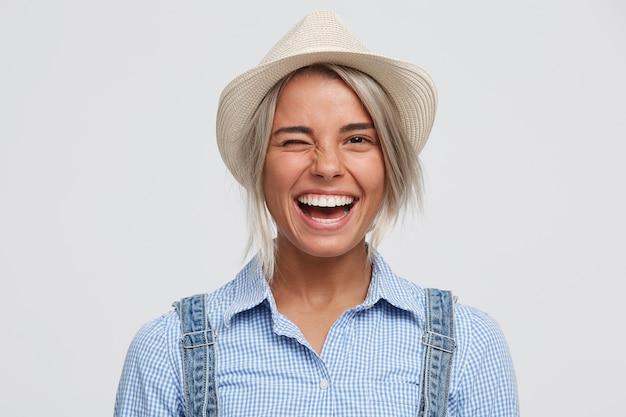 Wesoła Figlarna Szczęśliwa Dziewczyna W Kapeluszu Uśmiecha Się I Mruga W Pozytywnym Radosnym Nastroju Darmowe Zdjęcia