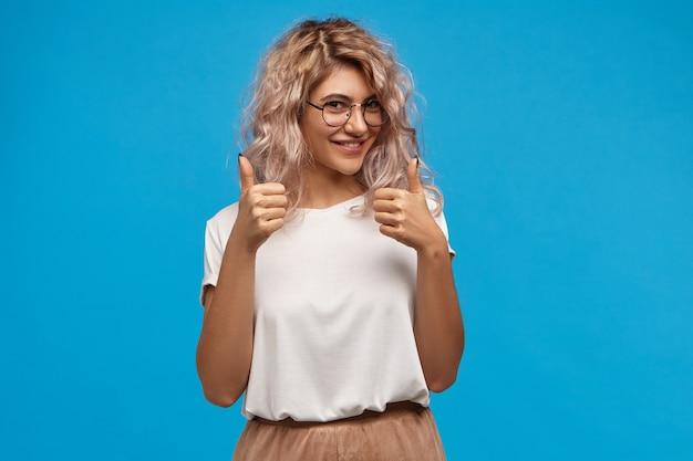 Wesoła Hipster Dziewczyna W Modnych Okrągłych Okularach, Robiąc Kciuk W Górę Gestem Obiema Rękami I Uśmiechając Się Radośnie, Pokazując Komuś Swoje Wsparcie I Szacunek, Mówiąc: Dobra Robota, Dobra Robota Darmowe Zdjęcia