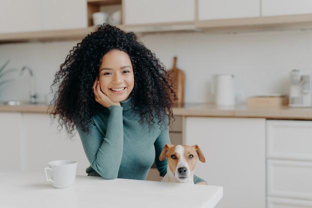 Wesoła kędzierzawa kobieta siedzi w kuchni, pije gorącą wodę, a jej lojalne zwierzę domowe pozuje cieszyć się spędzaniem razem czasu Premium Zdjęcia