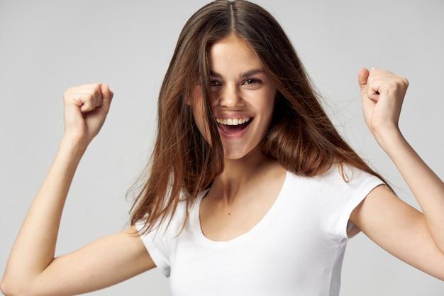 Wesoła Kobieta Biała Koszulka Emocji Ręce Zaciśnięte W Pięść Premium Zdjęcia