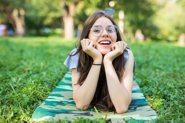 Wesoła Kobieta Ubrana W Jasną Sukienkę, Leżąc Na Trawie Darmowe Zdjęcia