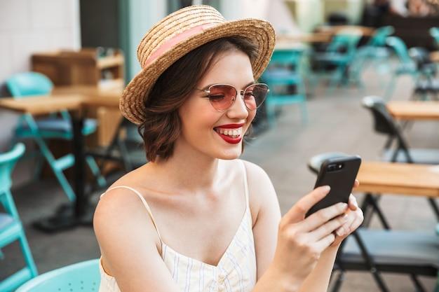 Wesoła Kobieta W Sukience I Słomkowym Kapeluszu Za Pomocą Smartfona Premium Zdjęcia