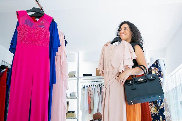 Wesoła Kupująca Kobieta, Stosując Sukienkę Z Wieszakiem I Patrząc W Lustro. Kobieta Wybiera Ubrania W Sklepie Z Modą. Koncepcja Zakupów Lub Sprzedaży Detalicznej Darmowe Zdjęcia