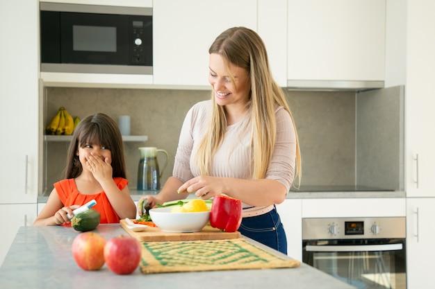 Wesoła Mama I Córka Rozmawiają I śmieją Się Podczas Gotowania Warzyw Na Obiad. Dziewczyna I Jej Matka Obierania I Krojenia Warzyw Na Sałatkę Na Blacie Kuchennym. Koncepcja Gotowania Rodziny Darmowe Zdjęcia