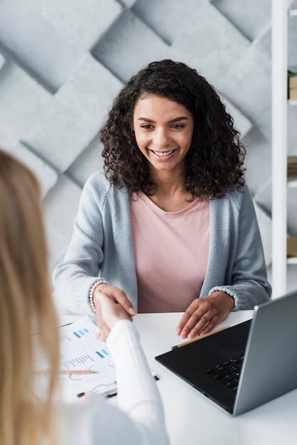 Wesoła młoda kobieta brunetka drżenie rąk z kolegą siedzi w biurze Darmowe Zdjęcia