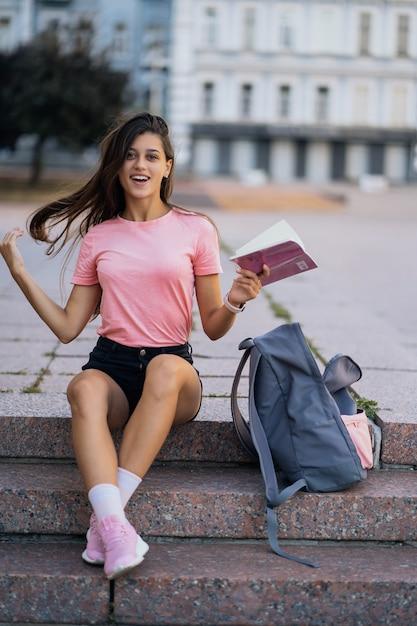 Wesoła Młoda Kobieta Robienie Notatek, Siedząc Na Schodach Otdoors Darmowe Zdjęcia