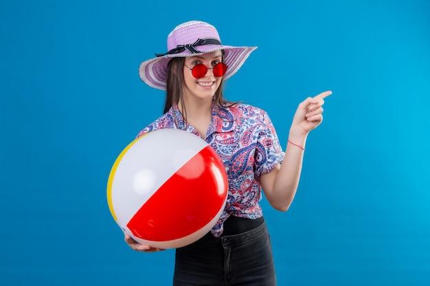 Wesoła Młoda Kobieta W Letnim Kapeluszu W Czerwonych Okularach Przeciwsłonecznych Trzymająca Nadmuchiwaną Piłkę Wskazującą Palcem W Bok, Uśmiechnięta Ze Szczęśliwą Twarzą Stojącą Nad Niebieską Przestrzenią Darmowe Zdjęcia