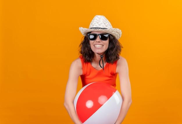 Wesoła Młoda Kobieta Z Krótkimi Włosami W Pomarańczowej Koszuli W Kapeluszu Przeciwsłonecznym I Okularach Przeciwsłonecznych Przytulająca Nadmuchiwaną Kolorową Piłkę Darmowe Zdjęcia