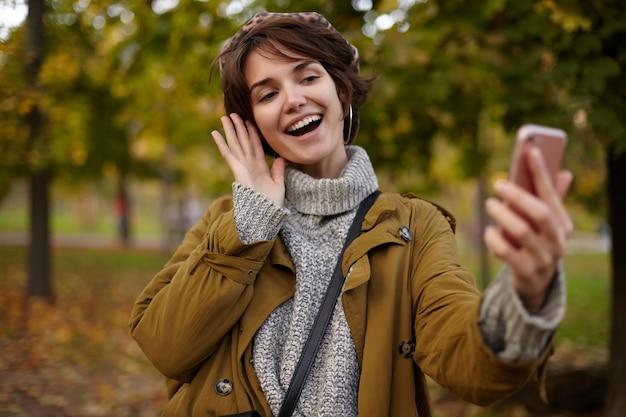 Wesoła Młoda śliczna Brązowowłosa Kobieta Z Przypadkową Fryzurą Podnosząca Rękę Z Telefonem Komórkowym Podczas Robienia Sobie Zdjęcia, Szeroko Uśmiechnięta, Pozująca Nad Pożółkłymi Drzewami Darmowe Zdjęcia