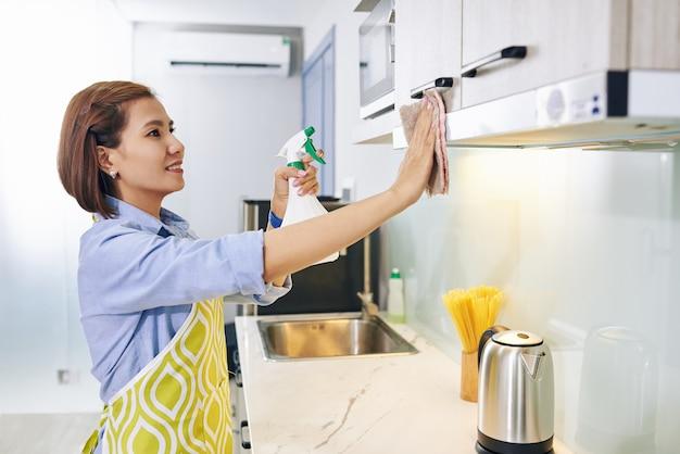 Wesoła Młoda Wietnamska Gospodyni Sprzątająca Szafki Kuchenne Sprayem Dezynfekującym Premium Zdjęcia