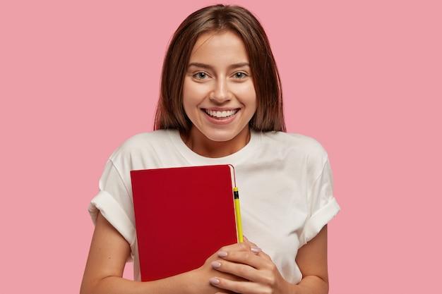 Wesoła Nastolatka Ma Zębaty Uśmiech, Zdrową Skórę, Długie Ciemne Włosy, Nosi Czerwony Notes Z Długopisem Darmowe Zdjęcia