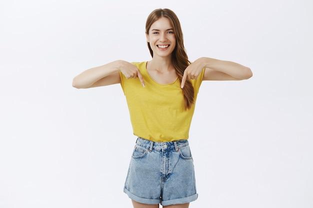 Wesoła Piękna Młoda Dziewczyna Pokazując Ogłoszenie Lub Logo, Skierowaną W Dół Darmowe Zdjęcia