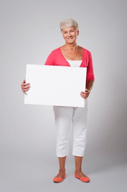 Wesoła Starsza Kobieta Trzyma Pustą Tablicę Darmowe Zdjęcia