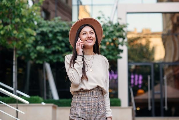 Wesoła Stylowa Kobieta Rozmawia Przez Telefon Komórkowy W Cityspace, Ciesząc Się Spacery Na świeżym Powietrzu. Premium Zdjęcia