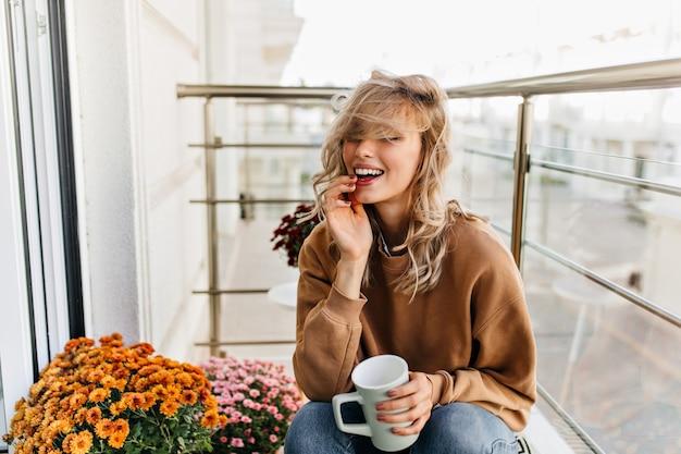 Wesołe Białe Dziewczyny Herbatę Na Balkonie. Wspaniała Młoda Kobieta Odpoczywa Na Tarasie. Darmowe Zdjęcia