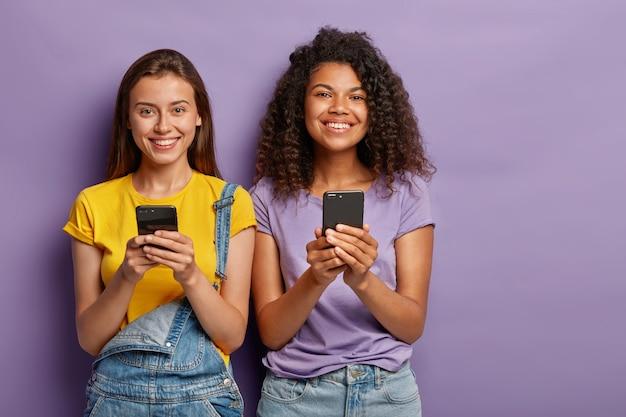 Wesołe Kobiety Rasy Mieszanej, Które Są Zawsze Online, Używają Telefonów Komórkowych Do Rozrywki I Rozmów W Sieciach Społecznościowych Darmowe Zdjęcia