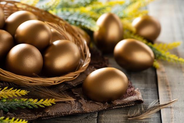 Wesołego Alleluja! Złoty Pisanek W Gnieździe I Pióro Na Drewniane Tła Premium Zdjęcia