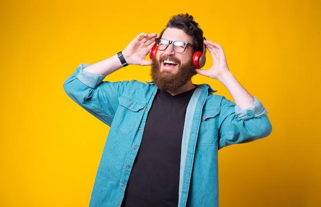 Wesoły Brodaty Hipster Słucha Muzyki Przez Słuchawki Na żółto Premium Zdjęcia