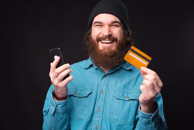 Wesoły Hipster Brodaty Mężczyzna Uśmiecha Się I Używa Karty Kredytowej I Smartfona Premium Zdjęcia