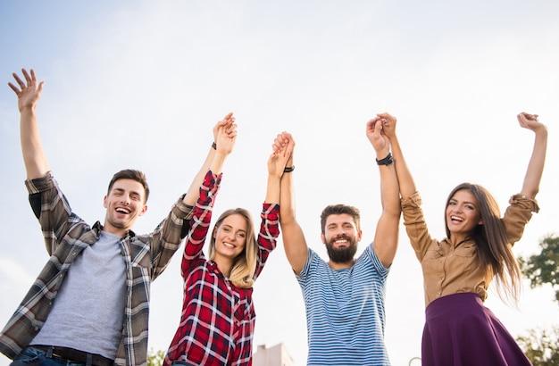 Wesoły ludzie podnieśli ręce do góry na ulicy. Premium Zdjęcia