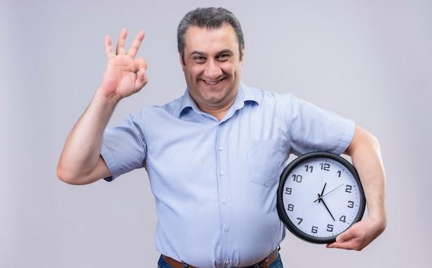 Wesoły Mężczyzna W średnim Wieku W Niebieskiej Koszuli W Pionowe Paski, Trzymając Duży Zegar Robi Ok Znak Palcami Darmowe Zdjęcia