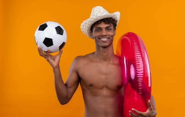 Wesoły Młody Przystojny Ciemnoskóry Mężczyzna Z Kręconymi Włosami W Kapeluszu Przeciwsłonecznym, Trzymając Nadmuchiwany Basen I Piłkę Nożną Darmowe Zdjęcia