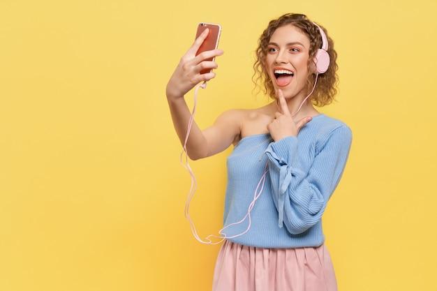 Wesoły Model Słuchania Muzyki Przez Słuchawki, Uśmiechając Się. Premium Zdjęcia