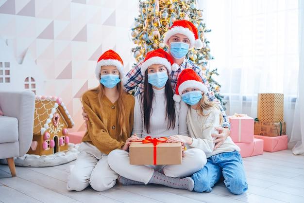 Wesołych świąt. Czteroosobowa Rodzina Z Prezentami Na Boże Narodzenie. Rodzice I Dzieci Noszą Maski Na Twarz Premium Zdjęcia