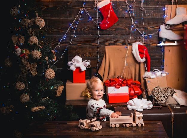 Wesołych świąt I Szczęśliwego Nowego Roku. śliczna Mała Dziewczynka Dekoruje Choinkę W Pomieszczeniu. Dostawa Prezentów świątecznych. Premium Zdjęcia