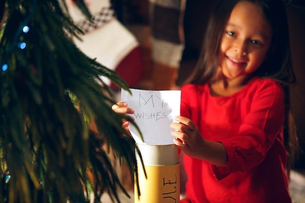 Wesołych świąt I Wesołych świąt. Słodkie Małe Dziecko Dziewczynka Pisze List Do świętego Mikołaja W Pobliżu Choinki W Domu W Domu. Wakacje, Dzieciństwo, Zima, Koncepcja Uroczystości Darmowe Zdjęcia