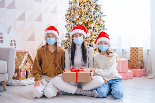 Wesołych świąt. Rodzina Mamy I Dzieci Z Prezentami Na Boże Narodzenie. Rodzice I Dzieci Noszą Maski Na Twarz Premium Zdjęcia