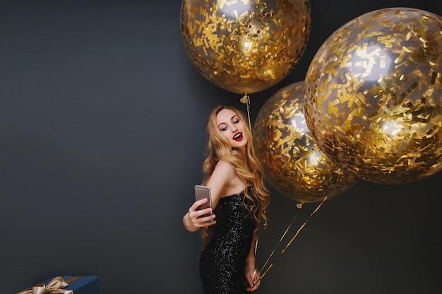 Wewnątrz Portret Oszałamiającej Jasnowłosej Dziewczyny Robiącej Selfie Na Uroczysty. Spektakularna Kobieta Z Balonów Imprezowych, Bawiąca Się I Robiąca Sobie Zdjęcie. Darmowe Zdjęcia