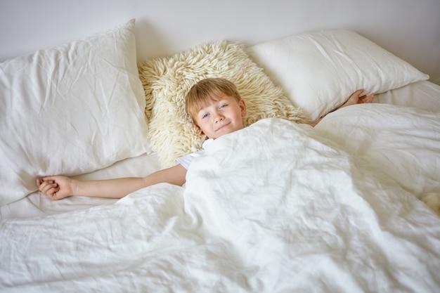 Wewnątrz Portret śpiącego Nastolatka Z Europy Wyciągającego Ramiona Po Przebudzeniu Wcześnie Rano, Leżącego Na Białej Pościeli, Idącego Do Szkoły, Patrzącego, Z Leniwym Wyrazem Twarzy Darmowe Zdjęcia