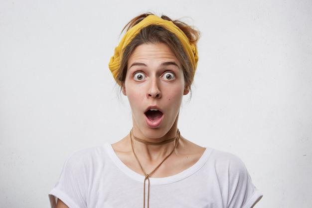 Wewnątrz Ujęcie ładnej Kobiety Wyglądającej Z Wyłupiastymi Oczami I Opuszczoną Szczęką, Noszącej żółty Szalik Na Głowie, Wisiorek I Białą Swobodną Koszulkę O Zdumionym Wyrazie Darmowe Zdjęcia
