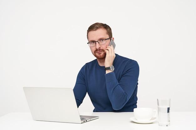 Wewnątrz Zdjęcie Młodego Brodatego Jasnowłosego Biznesmena, Trzymając Telefon Komórkowy W Uniesionej Ręce, Patrząc Zaskoczony Na Aparat, Siedząc Na Białym Tle Darmowe Zdjęcia
