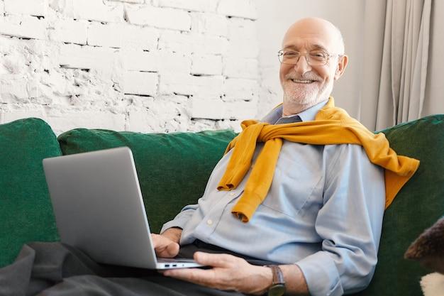 Wewnętrzne Zdjęcie Pozytywnie Atrakcyjnego Dziennikarza Płci Męskiej W Okularach I Eleganckich Ubraniach, Pracującego Nad Artykułem Biznesowym Do Gazety Internetowej Lub Bloga, Siedzącego Na Kanapie Z Laptopem I Uśmiechającego Się Do Kamery Darmowe Zdjęcia