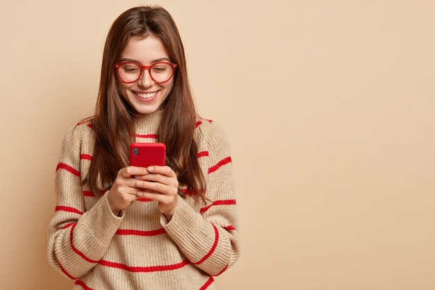 Wewnętrzne Zdjęcie Zadowolonych Nastolatek Tekstów Przez Komórkę, Czyta Ciekawy Artykuł Online, Nosi Swobodny Strój, Tworzy Nową Publikację Na Własnej Stronie Internetowej, Odizolowane Na Brązowej ścianie Z Wolną Przestrzenią Darmowe Zdjęcia
