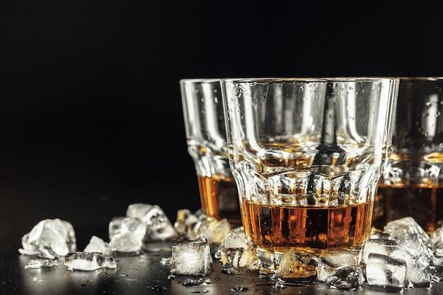 Whisky i lód na nieociosanym drewnianym tle Premium Zdjęcia