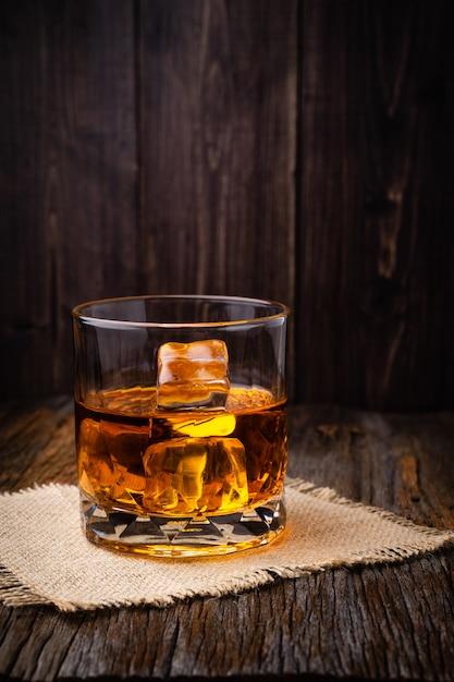 Whisky z kostką lodu w okularach na rustykalnym ciemny drewniany stół Premium Zdjęcia