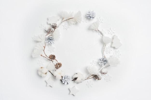 Wianek Bożonarodzeniowy Wykonany Z Drewnianych Płatków śniegu, Bawełnianych Kwiatków, Szyszek I Pomponów Z Białych Kwiatów. Premium Zdjęcia