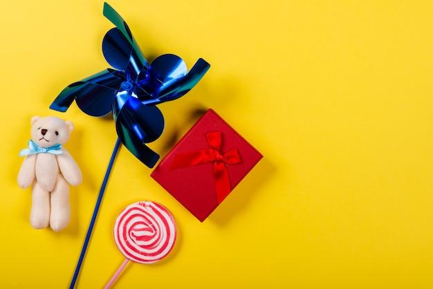 Wiatraczek, miś, lizak i prezent na żółto Premium Zdjęcia