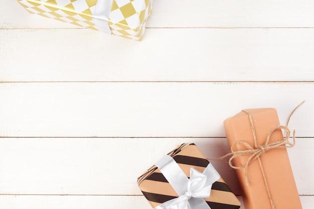 Wiązani łęku prezenta pudełka na białym drewnianym tle, odgórny widok Premium Zdjęcia