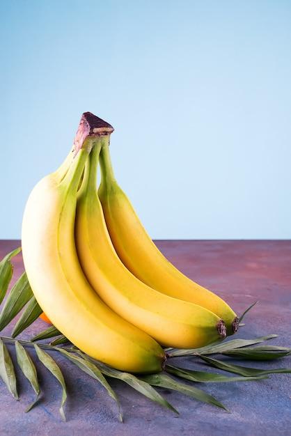 Wiązka banany z palmowym liściem na kamiennym tle z kopii przestrzenią Premium Zdjęcia