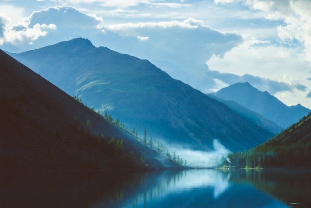Widmowy górski jezioro w średniogórzach przy wczesnym porankiem. piękne mgliste sylwetki gór i chmur odbite w czystej powierzchni wody. dym z ognisk. niesamowity krajobraz majestatycznej przyrody. Premium Zdjęcia