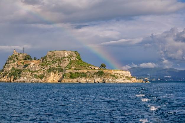 Widok Antyczny Venetian Forteca Na Wzgórzu Przy Corfu Wyspą, Grecja. Stare Kamienne ściany, Pokryte Zieloną Trawą, Zatoką Morską, Niebieskim Niebem I Tęczą Premium Zdjęcia