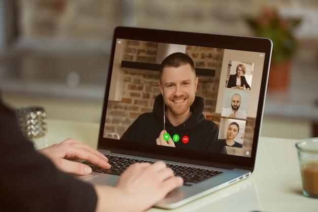 Widok Ekranu Laptopa Przez Ramię Kobiety. Dziewczyna Słucha Wypowiedzi Swoich Kolegów Na Odprawie Online Premium Zdjęcia
