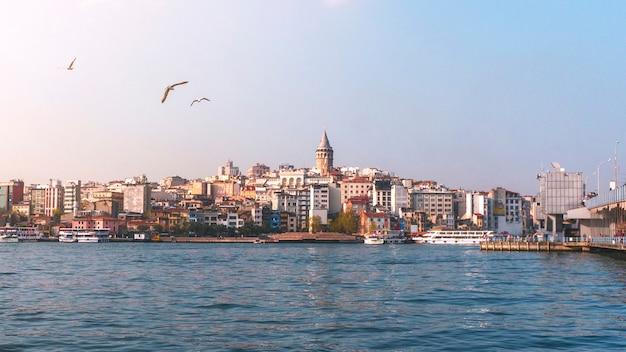 Widok istanbuł pejzażu miejskiego galata wierza z unosić się turystyczne łodzie w bosphorus, istanbuł turcja Premium Zdjęcia