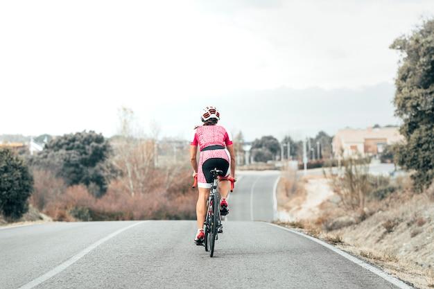 Widok Kobiety Rowerzysty Na Rowerze Do Wioski Z Tyłu Premium Zdjęcia